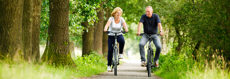 Foto van twee fietsers in bos op fietspad in Drenthe die een Arthuur fietsroute Drenthe fietsen.
