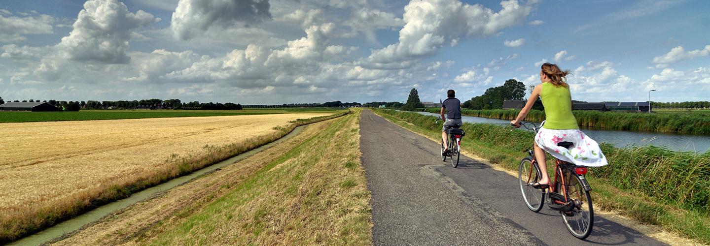 Twee fietsers die een Arthuur fietsroute fietsen lnags een kanaal.
